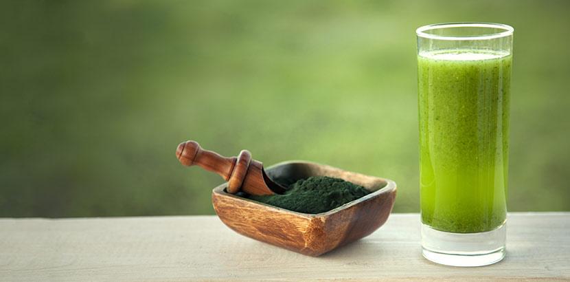 Spirulina Pulver neben einem Glas mit Spirulina Smoothie, einem Rezept mit Superfood.