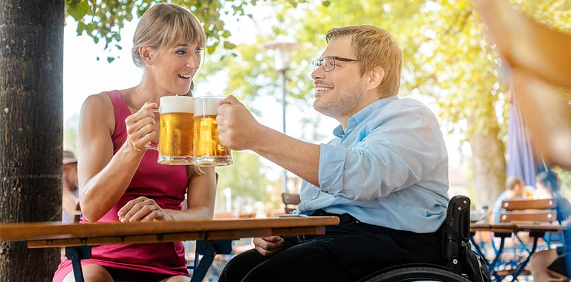 Mann im Rollstuhl mit Freundin in einem behindertengerechten Biergarten. Barrierefreie Lokale Wien.