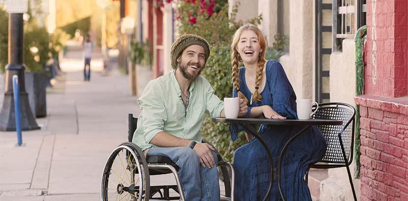 Junges Paar in einem Lokal; er sitzt im Rollstuhl. Beide lächeln die Kamera.