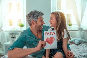 Kleines Mädchen, das ein Geschenk für Papa übergibt.