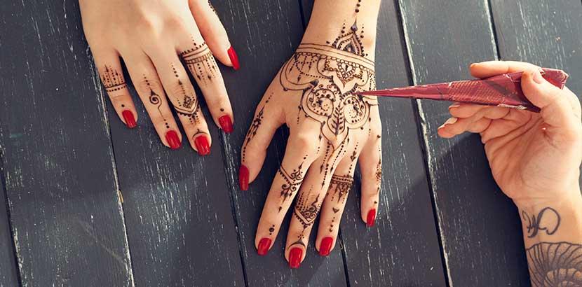 Hand einer Henna Künstlerin, die die Hände ihrer Kundin mit einem Henna Tattoo verziert.