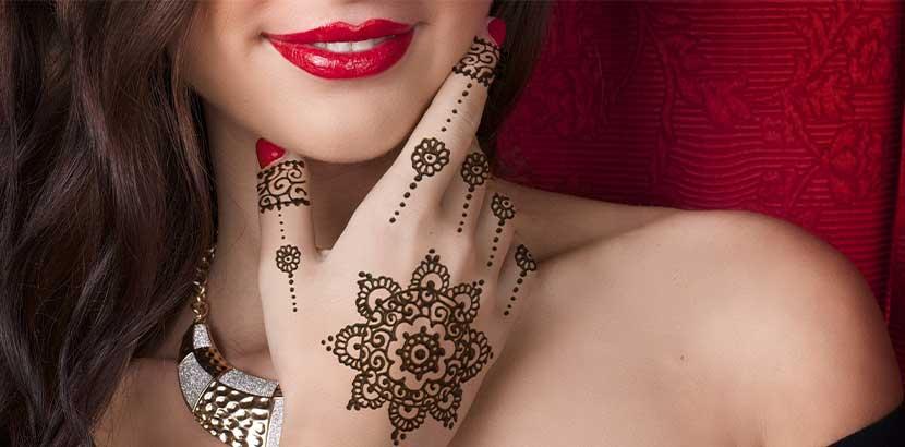 Junge hübsche Frau mit einem Henna Tattoo an der rechten Hand.