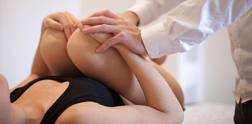 Junge Frau, die wegen Ischiasnerv Schmerzen beim Osteopathen behandelt wird.