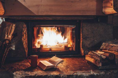 Gemütlicher Kachelofen mit Sichtfenster, vor dem ein aufgeschlagenes Buch und eine Tasse Tee stehen. Kennst du dich mit Kachelofen Preisen aus?
