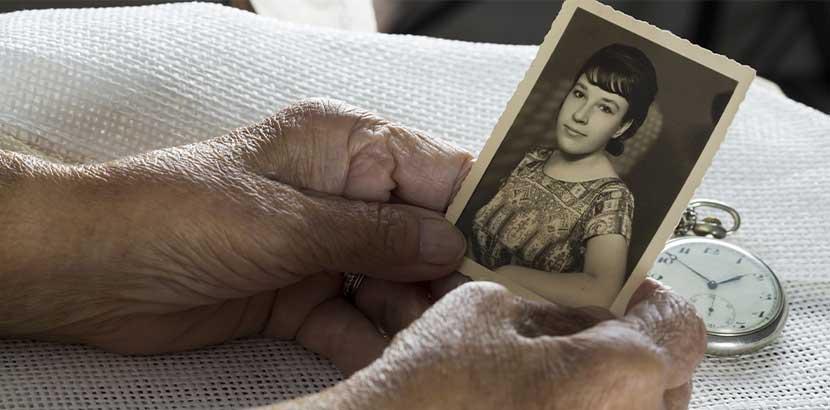 Hände eines älteren Menschen, der eine Schwarz-Weiß-Aufnahme von einer jungen Frau in den Händen hält. Körperspende Wien