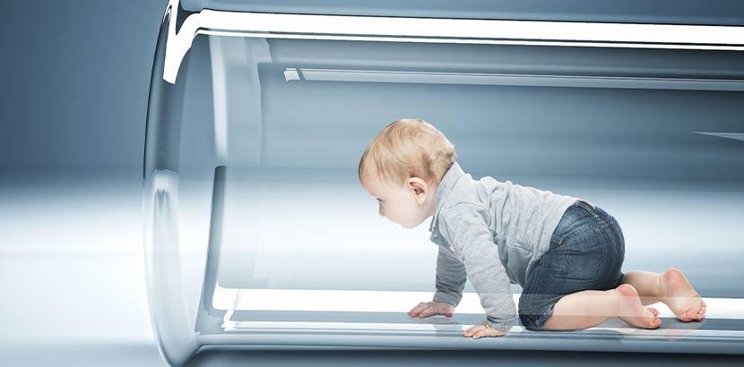 Kleinkind, das aus einem Reagenzglas herauskrabbelt. Künstliche Befruchtung Österreich.