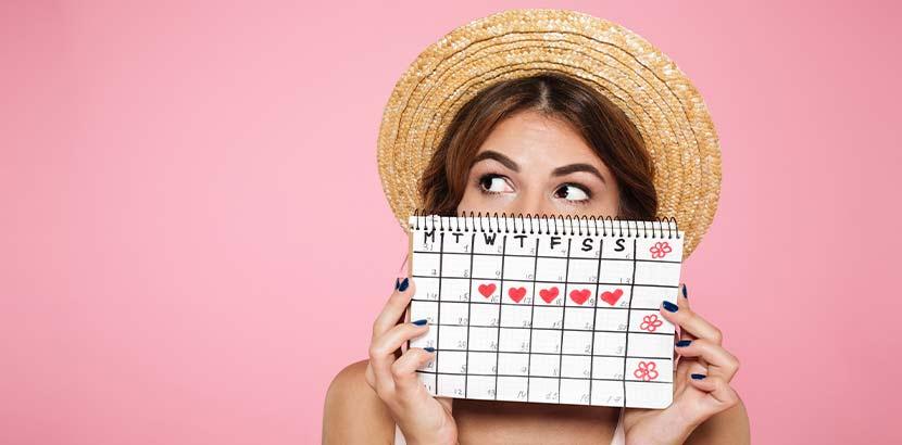 Junge Frau mit einem Kalender mit Menstruationszyklus vor ihrer Periode.
