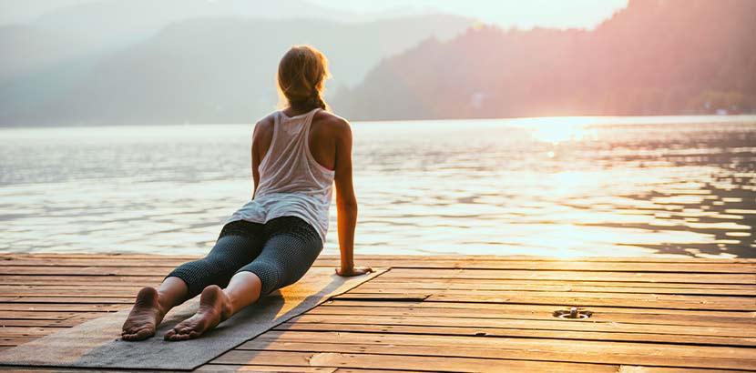 Junge blonde Frau, die am See Yoga macht, um ihre Periodenschmerzen zu lindern.