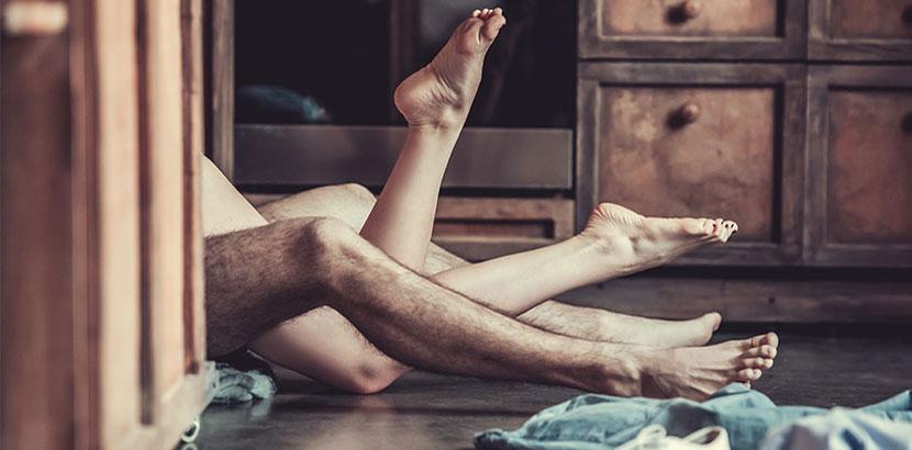 Ein Paar Frauenbeine und ein paar Männerbeine, die hinter einer Kommode aufeinander liegen. Verhütungsmethoden im Überblick.