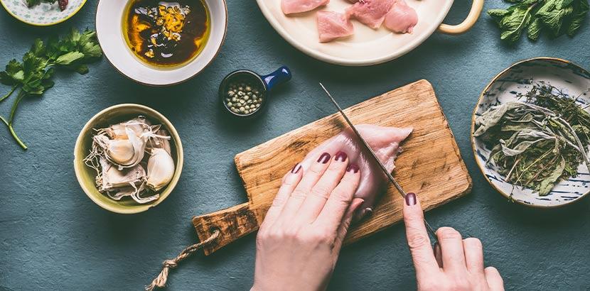 Frauenhände, die Fleisch schneiden. Ernährung gegen starke Regelschmerzen.