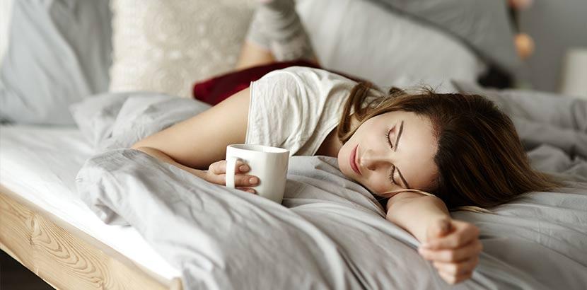 Junge Frau, die starke Regelschmerzen hat und diese mit Tee und anderen Hausmitteln lindert.