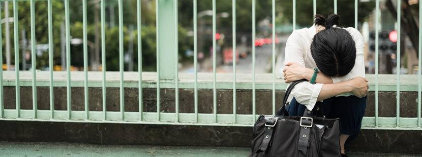 Junge schwarzhaarige Frau, die wegen starker Regelschmerzen am Wegesrand zusammengebrochen ist.