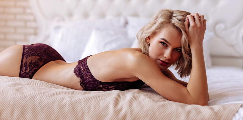 Dessous Wien: blondes Model in violettem Bralette und Slip