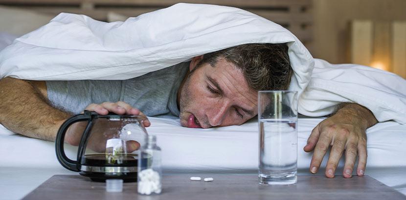 Mann mit Kater, der die Bettdecke über den Kopf gezogen hat, und vor dem Kaffee, ein Glas Wasser und Tabletten stehen. Was hilft gegen Kater?