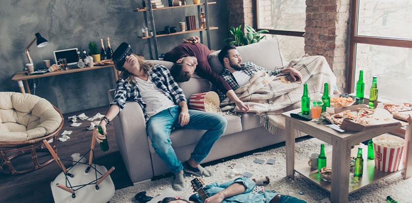 Vier Männer, die nach einer wilden Party im Wohnzimmer eingeschlafen sind und denen ein böser Morgen mit Kater bevorsteht. Was hilft gegen Kater?