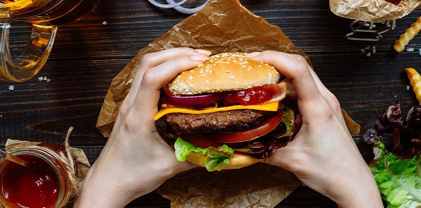 Frauenhände, die einen gut belegten Burger halten. Was hilft gegen Kater?