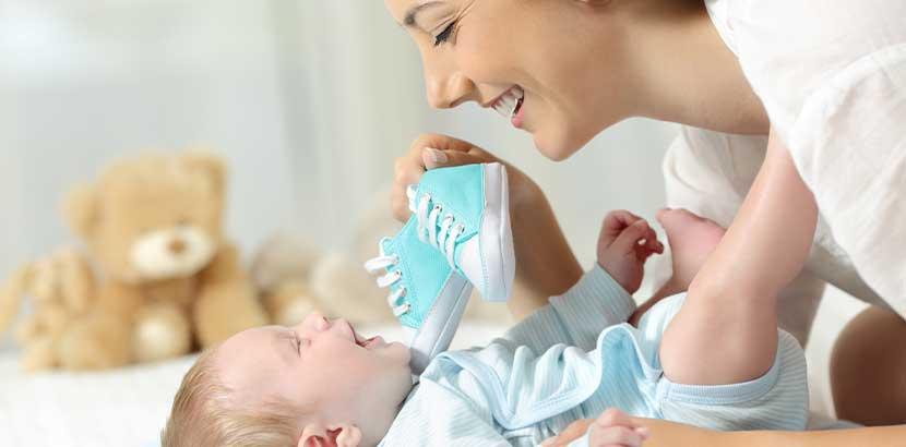 Mutter, die ihrem Baby die ersten Baby Schuhe zeigt. Baby Schuhe Wien.