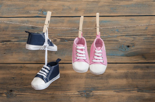 Zwei paar Baby Schuhe, ein blaues und ein rosanes, die an einer Wäscheleine hängen.