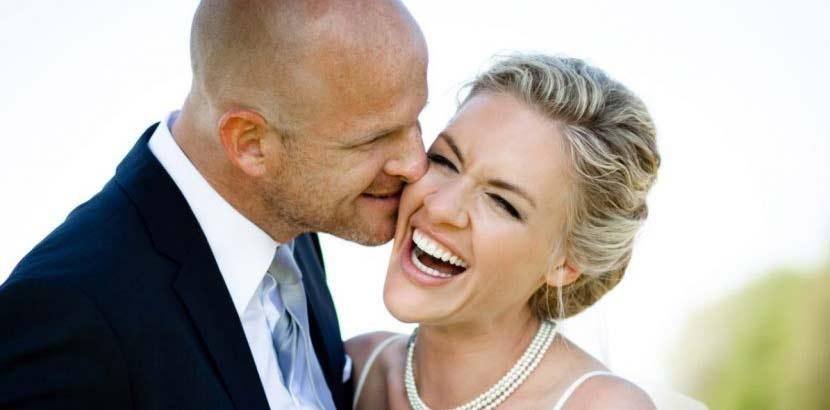 Junges hübsches Brautpaar; Bräutigam küsst seine Braut auf die Wange.