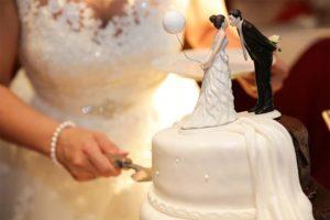 Braut, die gemäß der Hochzeitstradition die Hochzeitstorte anschneidet. Hochzeitsbräuche aus aller Welt.