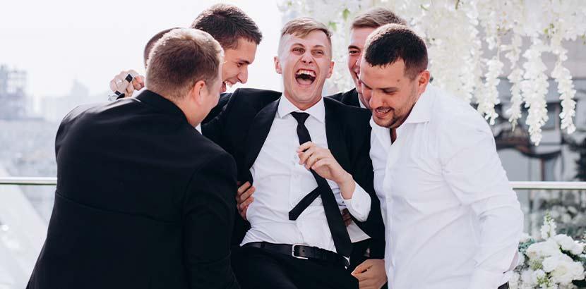 Gruppe von jungen Männern, die gemäß der Hochzeitsbräuche den Junggesellenabschied feiern.