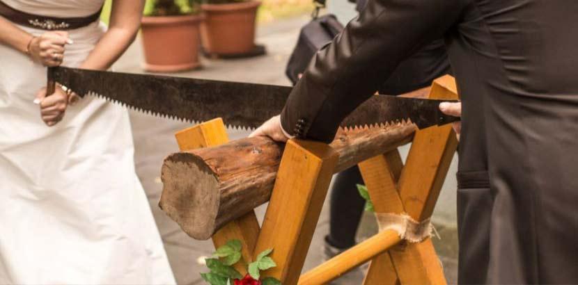 Brautpaar, das gemäß der Hochzeitsbräuche direkt nach der Trauung einen Baumstamm zersägt.