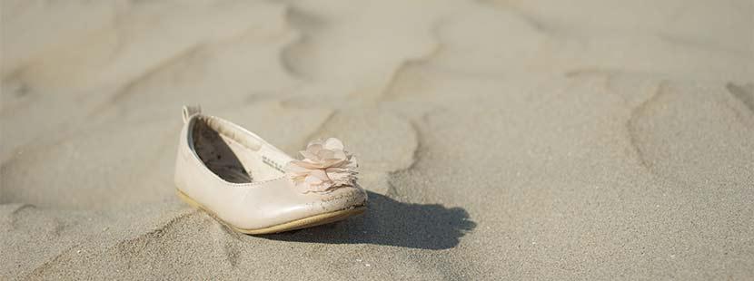 Vintage Brautschuhe, der vergessen im Sand liegt.