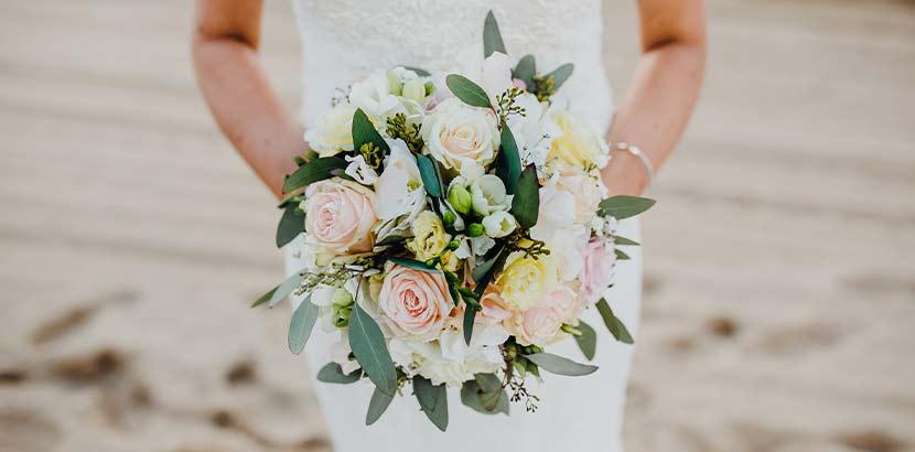Braut in weißem Kleid, die gemäß der Hochzeitsbräuche ihren Brautstrauß wirft.
