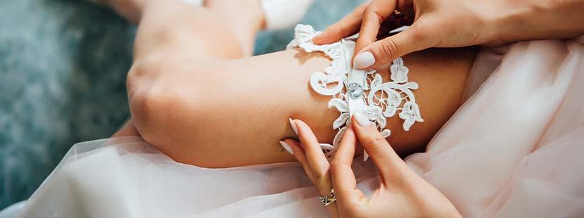 Junge Braut mit schönen Beinen, die im Sinne der Hochzeitsbräuche ein hellblaues Strumpfband anlegt.