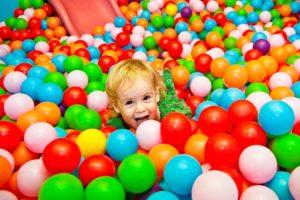 Kleines blondes Mädchen im Bällebad im Indoorspielplatz.