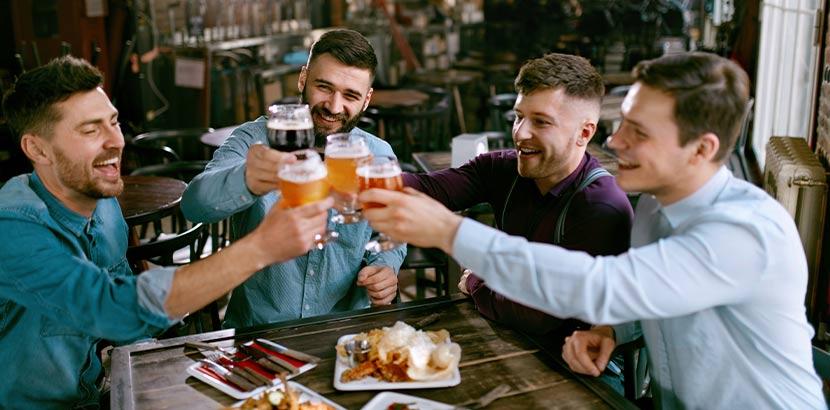 Vier Männer, die beim Junggesellenabschied in Wien in einem Pub anstoßen.