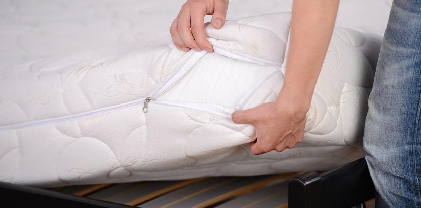 Matratze reinigen: Eine Person bezieht eine Matratze mit einem Matratzenschoner.
