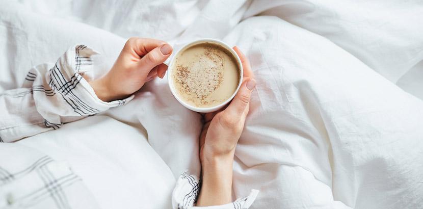 Matratze reinigen: Eine Frau trinkt Kaffee im Bett