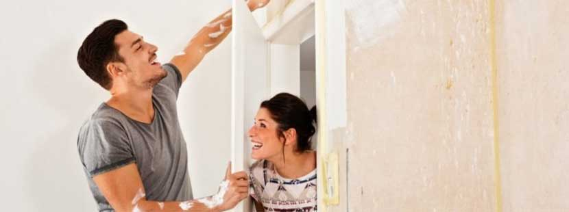 Junges Paar beim Rigips streichen in der ersten eigenen Wohnung.