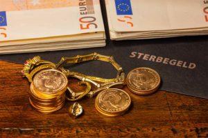 Goldschmuck, Münzen und große Geldscheine auf einer Mappe, in der die Sterbegeldversicherung aufbewahrt wird.