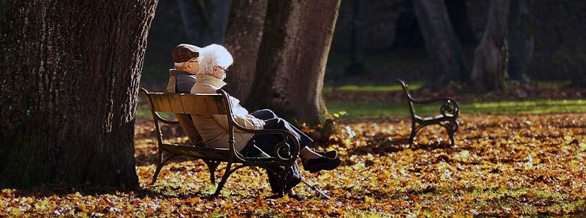Altes Ehepaar, das im Herbst auf einer Bank sitzt und über Sterbgeldversichungen spricht.