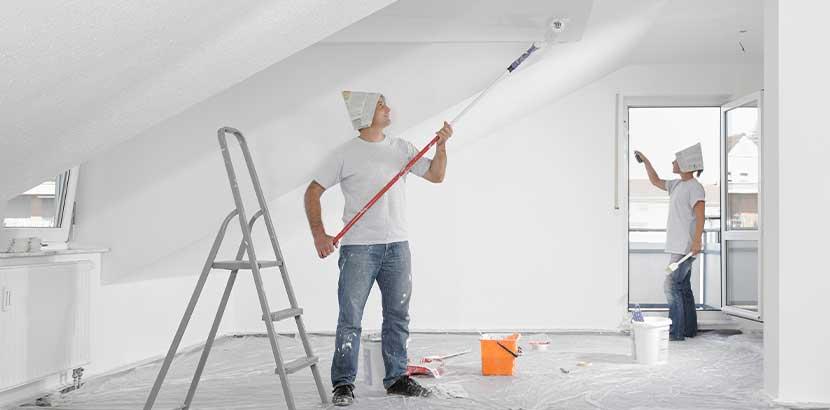 Pärchen, das gemeinsam einen frisch mit Rigipsplatten ausgebauten Dachboden streicht.
