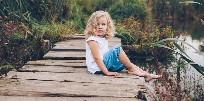Kleines blondes Mädchen auf einem Holzsteg im Hochmoor.