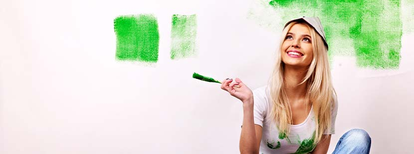 Junge blonde Frau, die eine Wand mit Wandlack in verschiedenen Farben gestrichen hat.