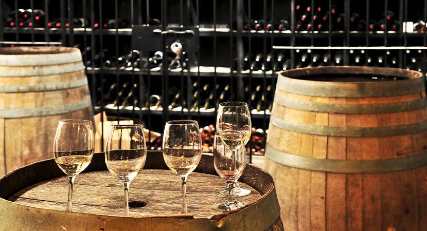 Weinkeller bauen: Ein Weinkeller mit Weinfässern und Weinflaschen.