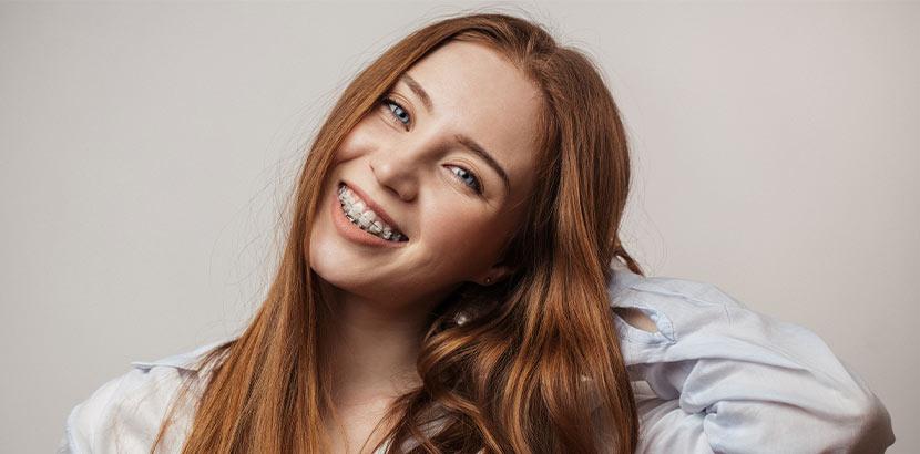 Hübsche junge Frau mit roten Haaren und Zahnspange Brackets.