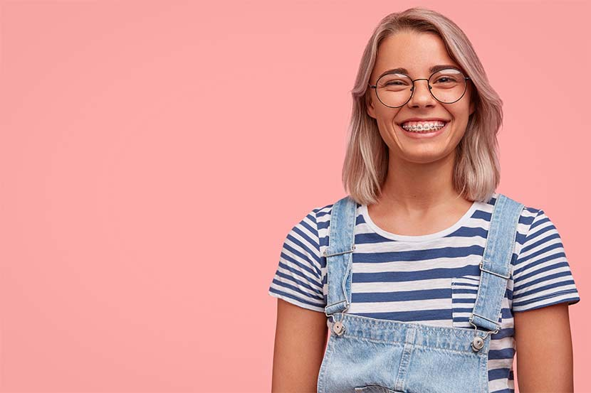 Junge blonde Frau in Latzhose und mit Zahnspange vor rosa Hintergrund.