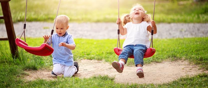 Gartenmöbel für Kinder: Zwei Kinder spielen auf einer Kinderschaukel aus Holz und Kunststoff.