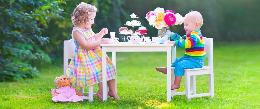 Gartenmöbel Kinder: Zwei Geschwister sitzen draußen auf Gartensesseln und spielen zusammen ein Garten Spiel.