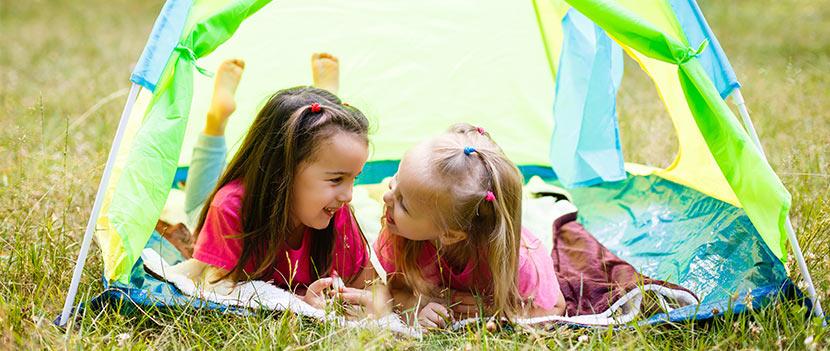 Gartenmöbel für Kinder: zwei kleine Mädchen spielen in einem Kinderzelt im Garten