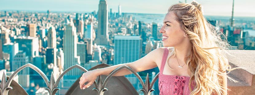Haare bleichen und aufhellen: Eine Frau mit blonden Haaren steht auf einem Aussichtsplateau.