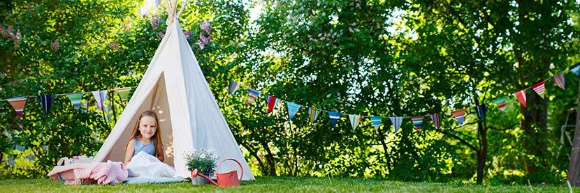 Kindermöbel Garten: Ein Mädchen sitzt in einem Zelt im Garten.