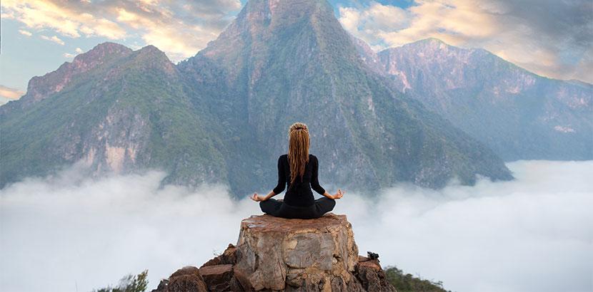 Junge Frau, die mit dem Rücken zur Kamera auf einer Bergspitze sitzt und meditiert. Meditation Wien.