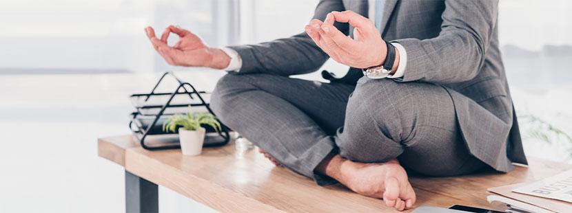 Geschäftsmann, der im Büro auf dem Schreibtisch sitzt und meditiert. Meditation Wien.