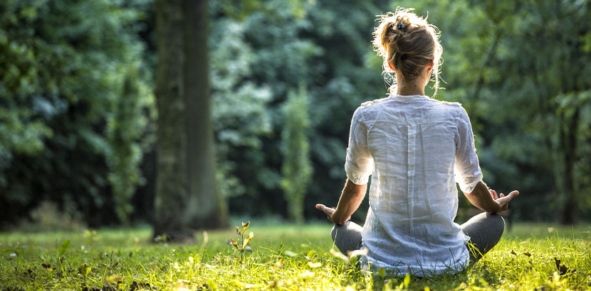 Junge Frau, die mit dem Rücken zur Kamera auf einer grünen Wiese sitzt und meditiert. Meditation Wien.
